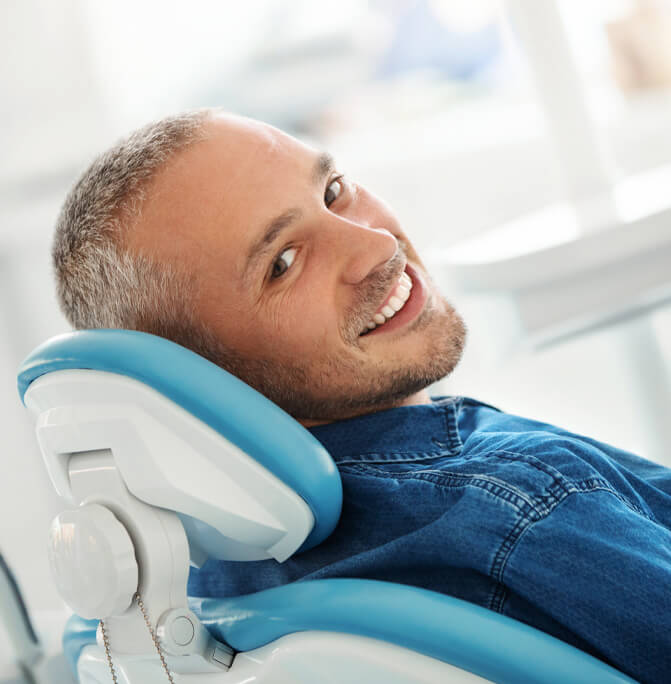 smiling man laying back in a dental chair