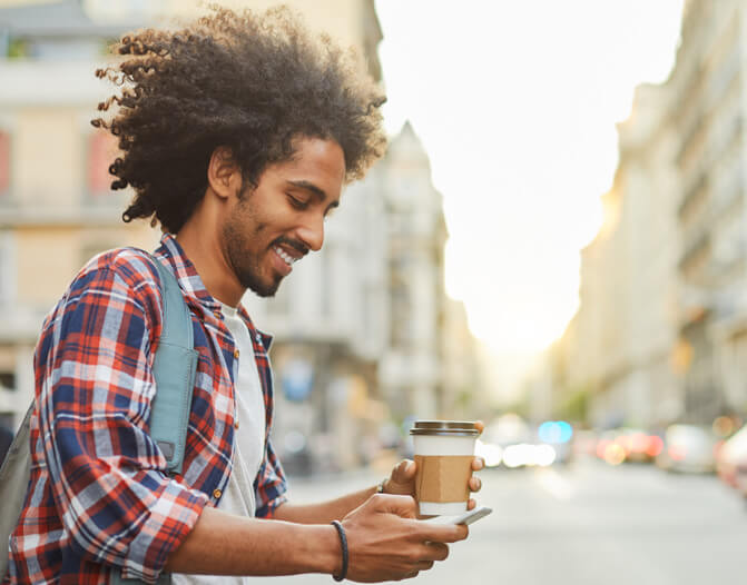 smiling man standing on sidewalk holding a coffee, looking at his phone