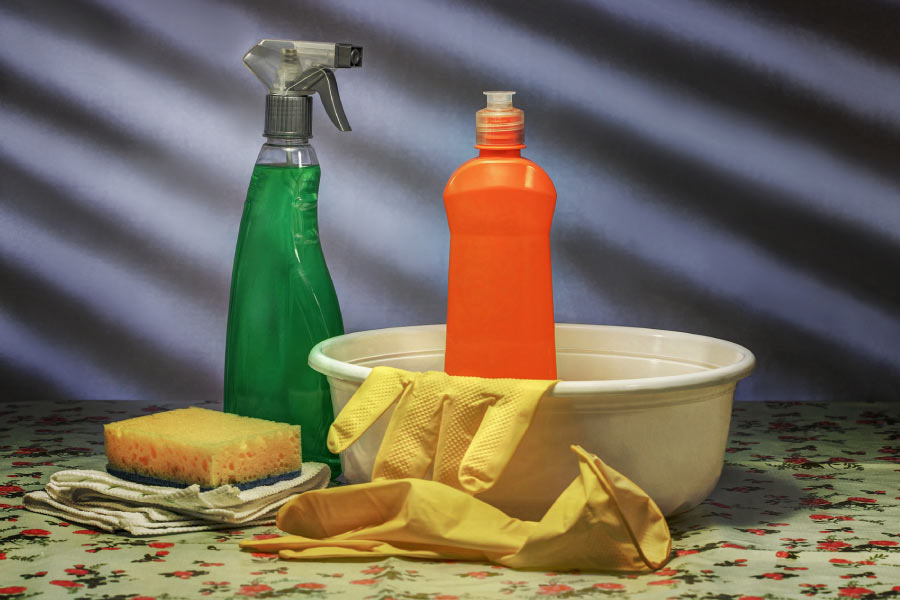 Photo of cleaning supplies including bowl, sponge, rubber gloves, spray bottle and soap