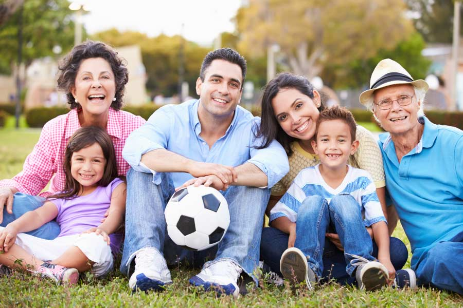 Smiling multigenerational Hispanic family sitting on the grass with a soccer ball