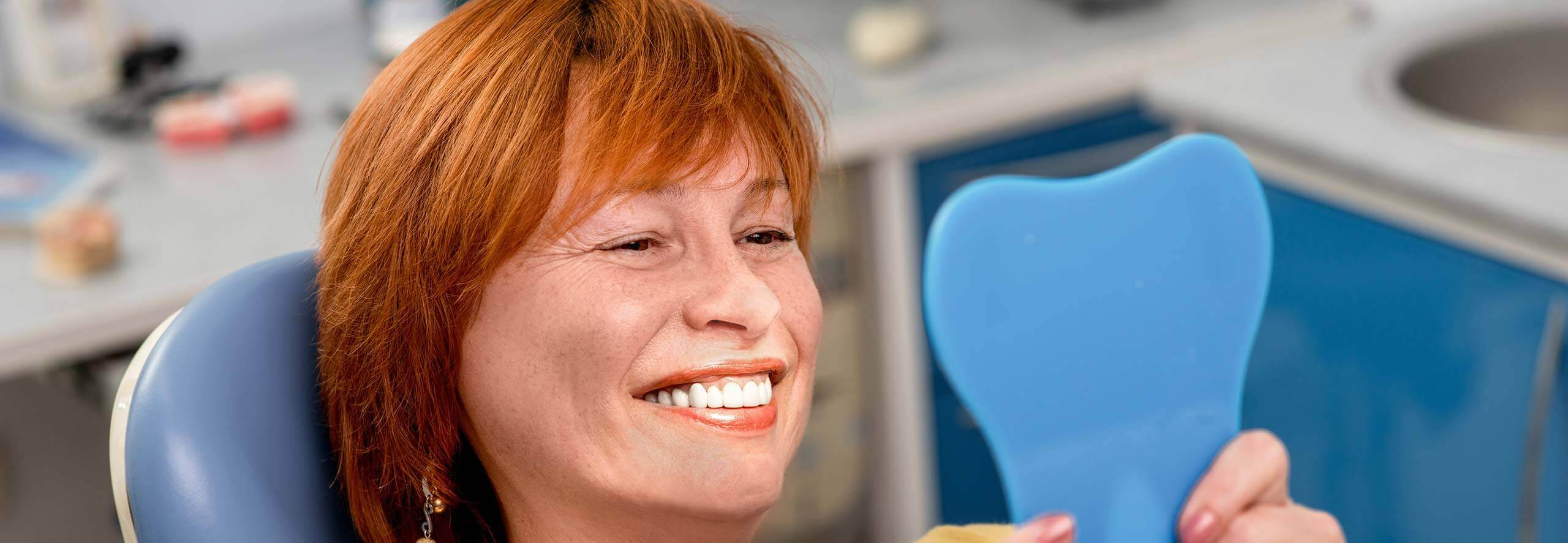 woman examining her smile in a mirror